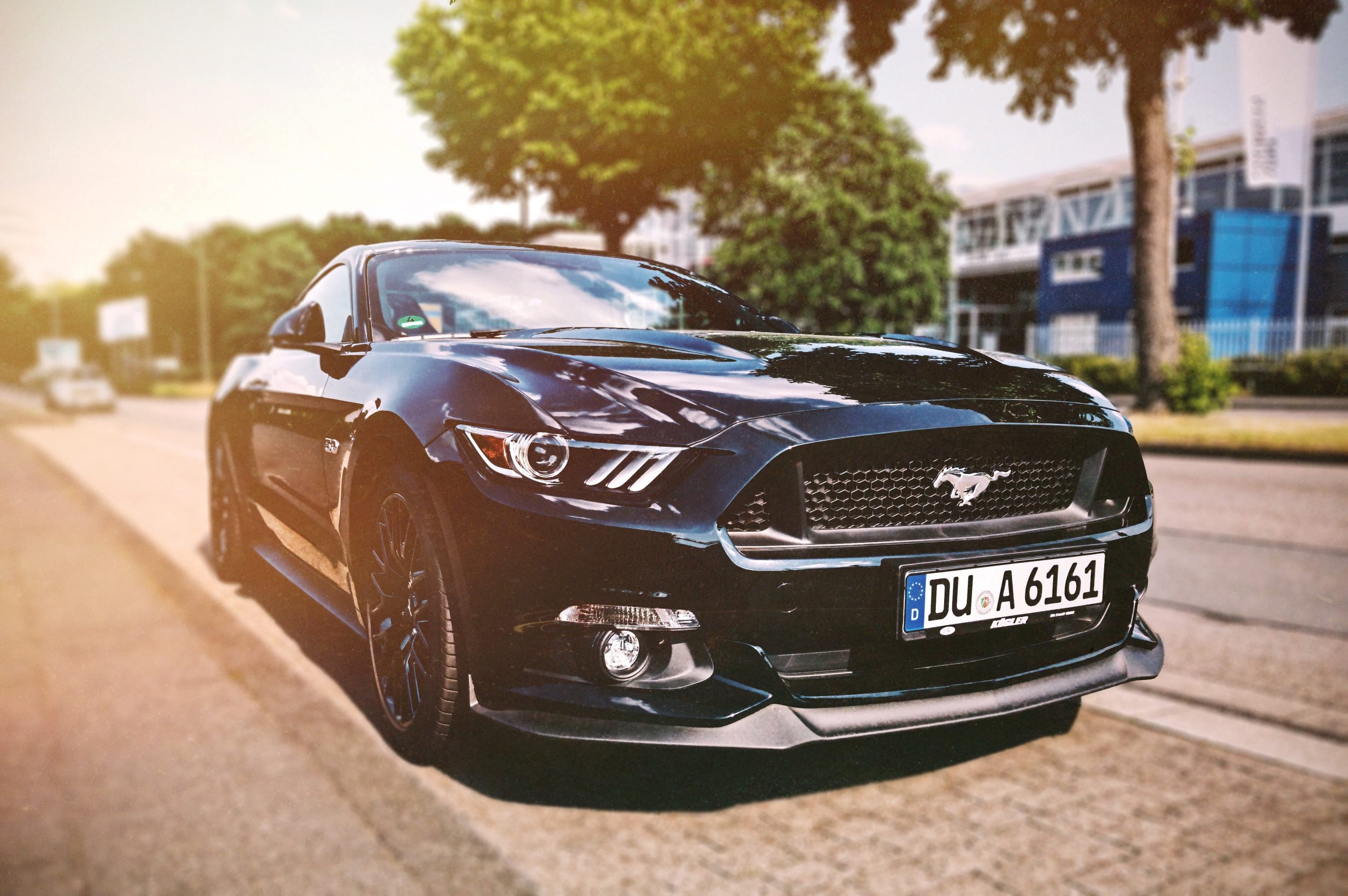 wallpaper Black Mustang sports car parked beside the street