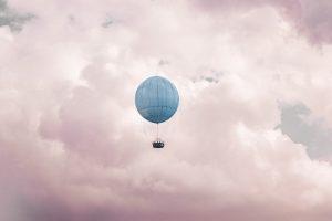 Blue hot air balloon on clouds