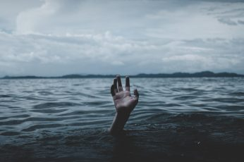 Grayscale photography of hands underbody of water