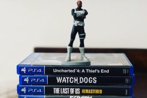 Assorted-title Sony PS4 game cases with figurine on top