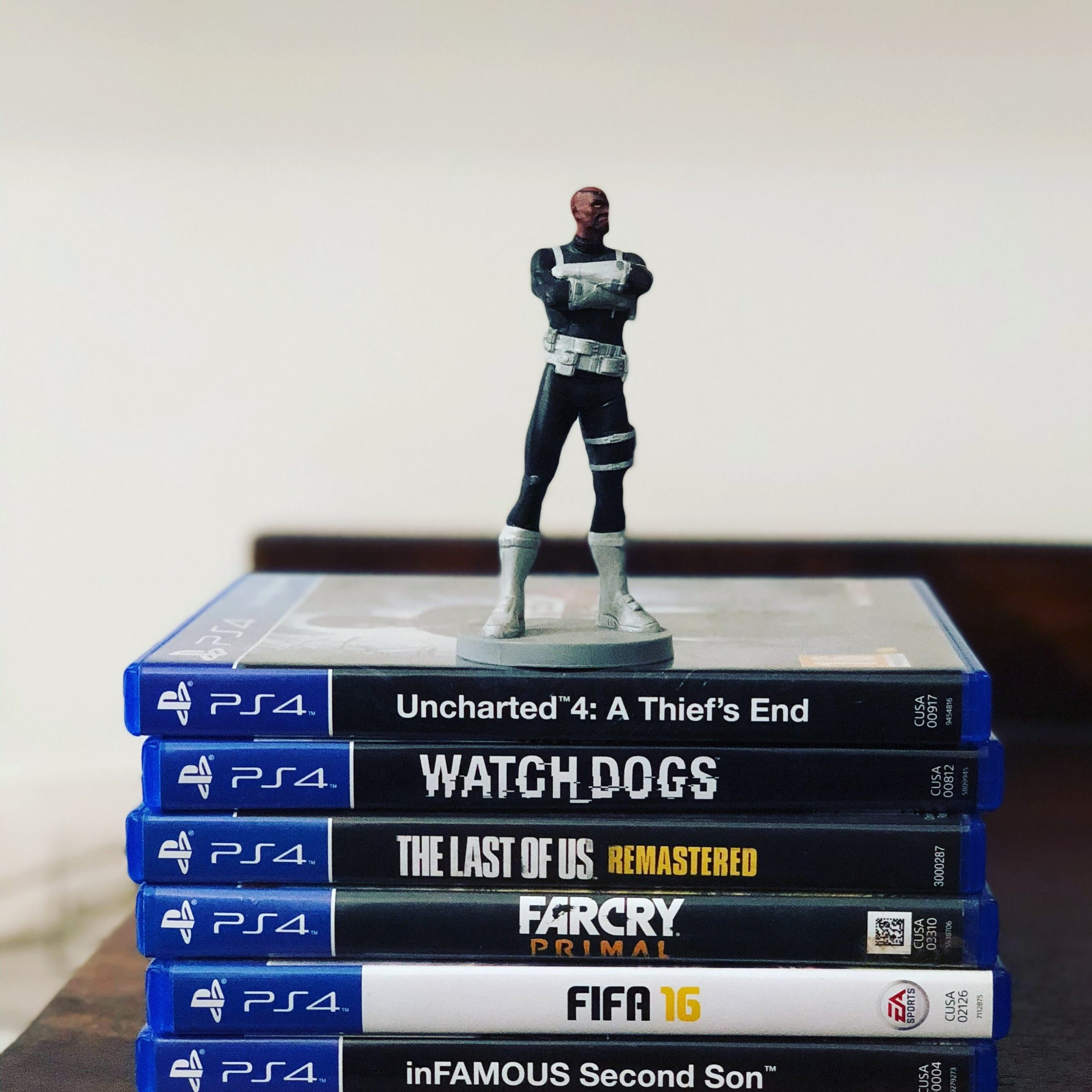wallpaper Assorted-title Sony PS4 game cases with figurine on top