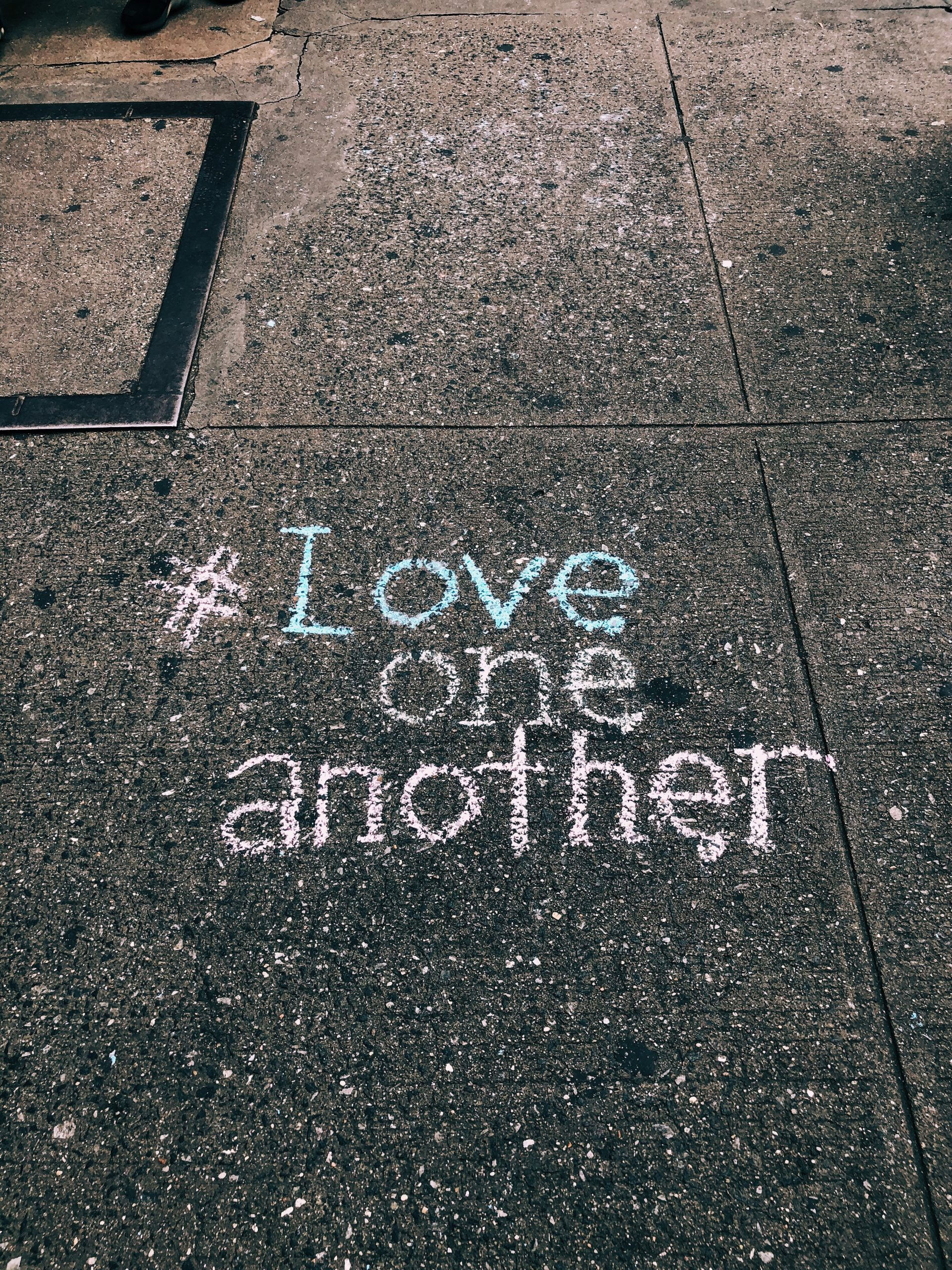 wallpaper Love one another chalk written on concrete floor