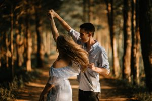 Man and woman dancing at center of trees