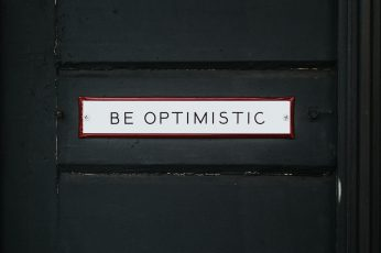 Black wooden door with be optimistic text overlay