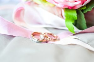 Silver-and-gold-colored rings near pink flower