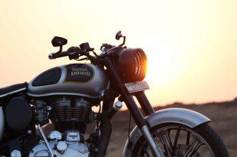 Black and grey Royal Enfield motorcycle on brown field, bullet wallpaper
