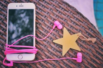 Wallpaper rose gold iPhone 6 with pink earphones on brown wicker table