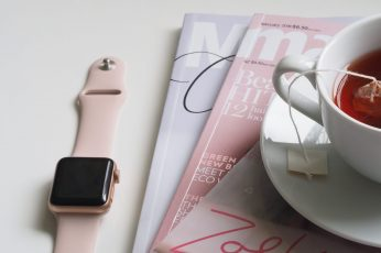 rose gold aluminum case Apple Watch with pink Sport Band beside white ceramic teacup filled with red liquid placed on white wooden board