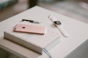 Wallpaper rose gold iPhone 6s on white book near gold aluminum case Apple Watch