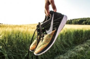 Wallpaper person holding pair of black-and-yellow Nike running shoes