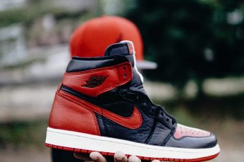 Wallpaper selective focus photo of person holding unpaired black and red Nike Air Jordan 1 shoe