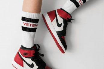 Wallpaper person wearing pair of black toe Air Jordan 1's, white-red-and-black Nike Air Jordan 1's