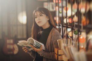 Woman in brown cardigan holding book behind black metal book rack wallpaper