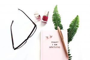 Eyeglasses and cosmetic bottle, book, pen, fern, nail varnish wallpaper
