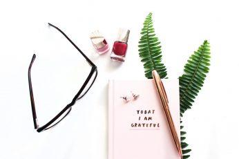 Eyeglasses and cosmetic bottle, book, pen, fern, nail varnish wallpaper