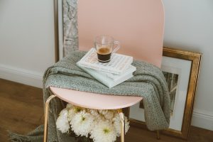 Clear glass mug on three stacked books inside room, pink chair with gray scarf over books and clear glass mug