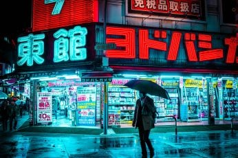 Man holding umbrella walking on the street near store during nighttime wallpaper