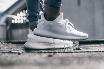 Person wearing pair of cream white Adidas Yeezy Boost 350 shoes wallpaper