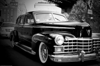 Grayscale photography of classic car on road beside street sign wallpaper