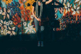 Woman wearing blue jeans leaning on mural wall, girl, model