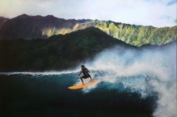 Man riding surf on sea near mountain, hawaii, hawaii, Surfer