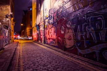 City side street with street art and graffiti captured by night wallpaper