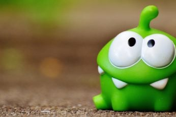 Green cut the rope frog toy on brown surface, figure, funny wallpaper